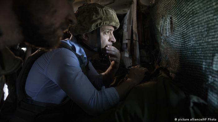 Presidente Volodimir Zelenski de capacete militar olha preocupado através de buraco