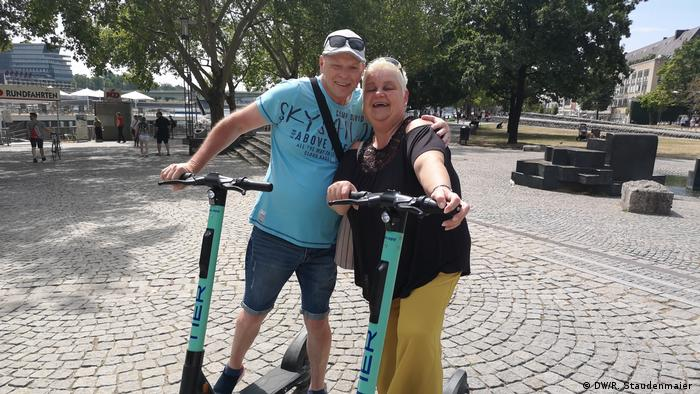 Anja Rehorst and her husband pose with their rented E-Scooters in Cologne, Germany (DW/R. Staudenmaier )