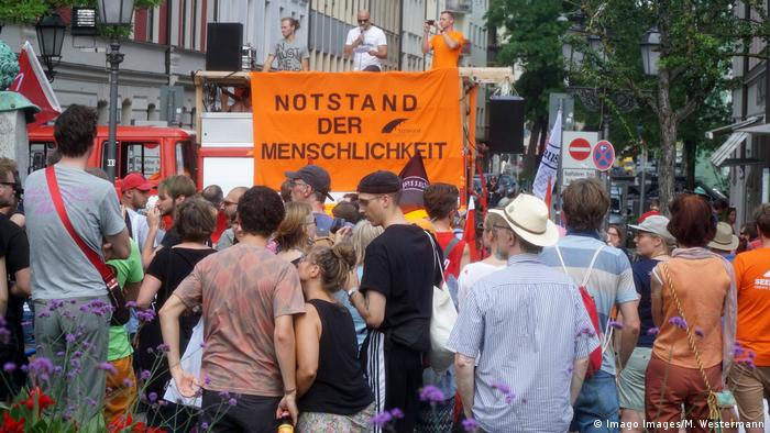 Demonstrators holding up placard (Imago Images/M. Westermann)