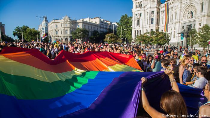 Protesters hold up a rainbow flag (picture-alliance/dpa/L. Lizana)