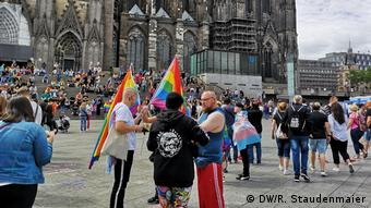 People gather with rainbow flags in front of Cologne Cathedral