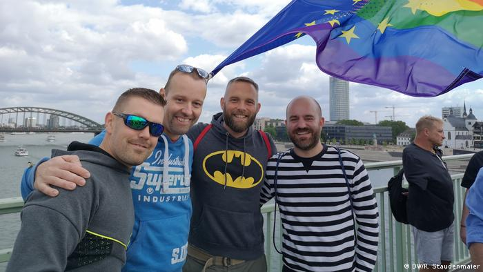 A group of men with a European Union flag with its colors merged with the rainbow flag