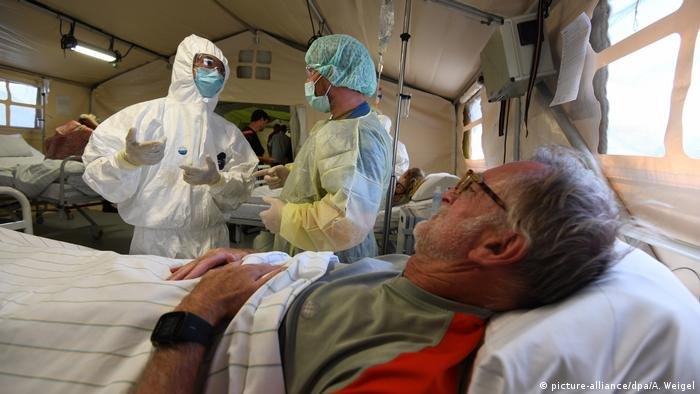 A Chinese and German soldier discuss next to a patient (picture-alliance/dpa/A. Weigel)