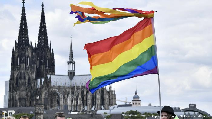 A rainbow flag in front of the cathedral in Cologne, Germany