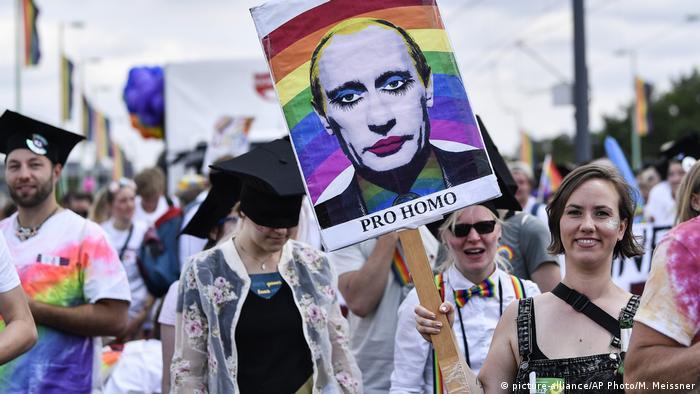Parada do Orgulho Gay em Colônia: mulher ergue cartaz com Vladimir Putin maquiado, diante de arco-iris LGBT