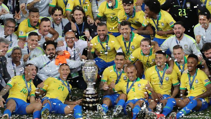 Jogadores e comissão técnica posa para fotógrafos com o troféu de campeão da Copa América