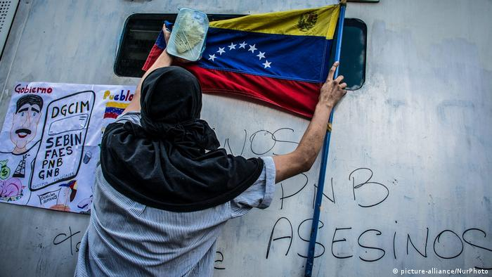 A supporter of opposition leader Juan Guaido looks through a barricade during a demonstration