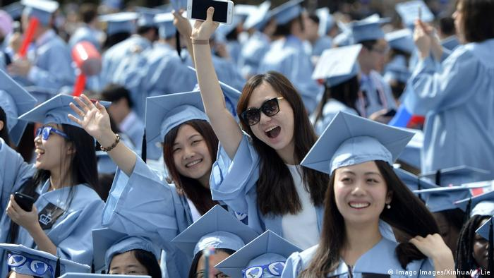 Crowd of Columbia University graduates in blue caps and gowns, a few girls cheering and laughing