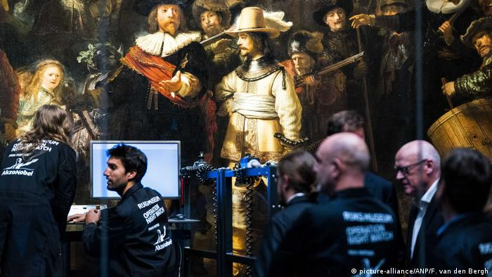 Restorers sitting in front of the painting The Night Watch