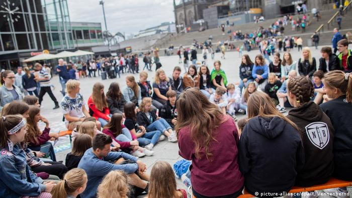 A group of student protesters take part in a climate change demonstration outside of the main train station in Cologne, Germany
