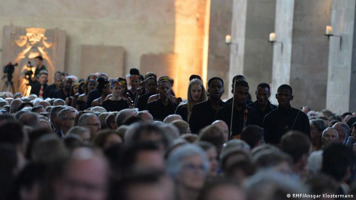 Musicians proceed down the aisle of an ancient basilica, flanked by seated audience