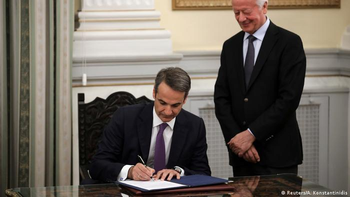 Kyriakos Mitsotakis signsma document during his swearing in ceremony as prime minister