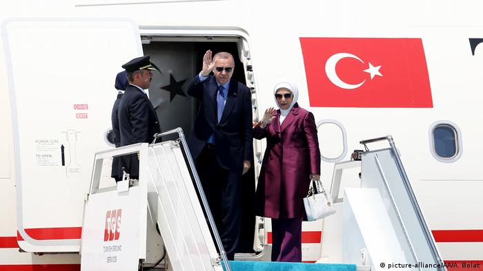 Turkey's president and his wife wave from the door of their plane