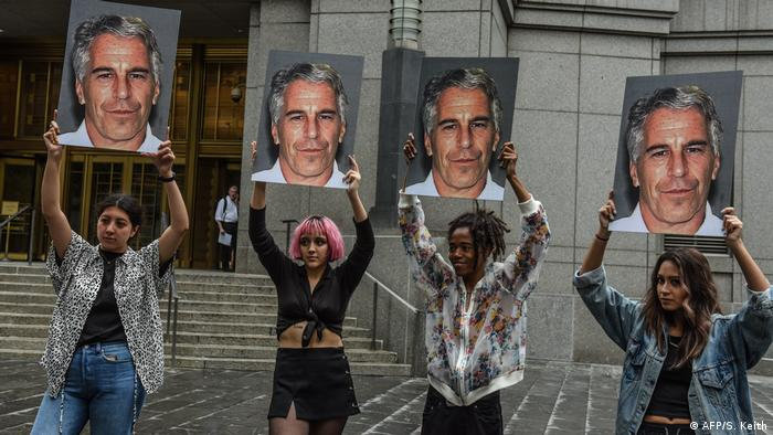 A protest group called Hot Mess hold up signs of Jeffrey Epstein in front of the Federal courthouse in New York