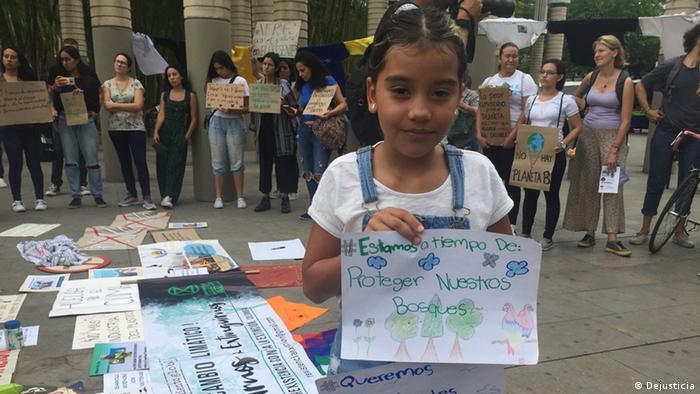 Menina mostra desenho pedindo proteção de bosques