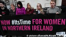 Demonstraters hold a banner that reads, Now #ItsTime for women in Northern Ireland