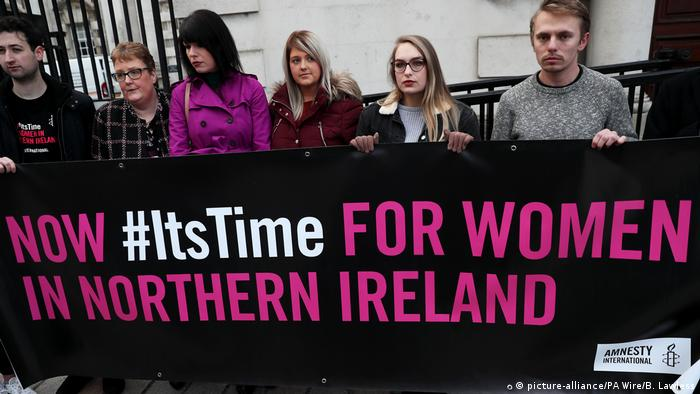 Protesters stand in front of the court as a judicial review of Northern Ireland's abortion alws gets started