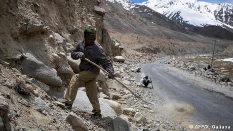 A road maintenance worker shovels soil by a mountainside along Pangong Lake road near the Chang La pass in India's Ladakh region