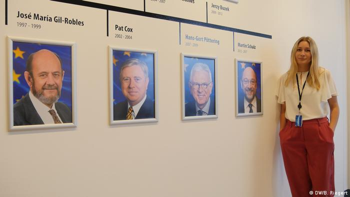 Kira Peter-Hansen, the youngest-ever MEP, standing alongside photos of former Parliament presidents