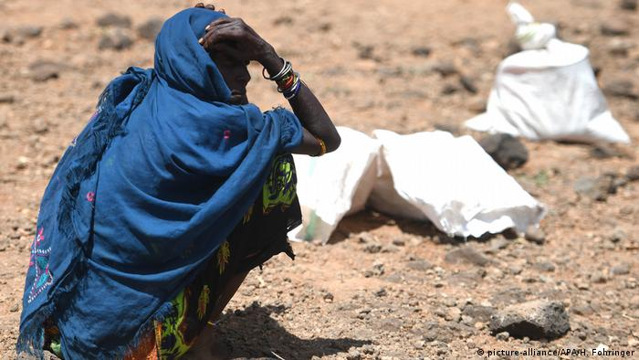 A woman sits while waiting for food to be distributed in Kenya