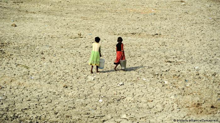 Crianças carregando água em solo ressecado