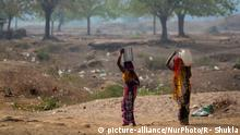 Two women carry drinking water on their heads