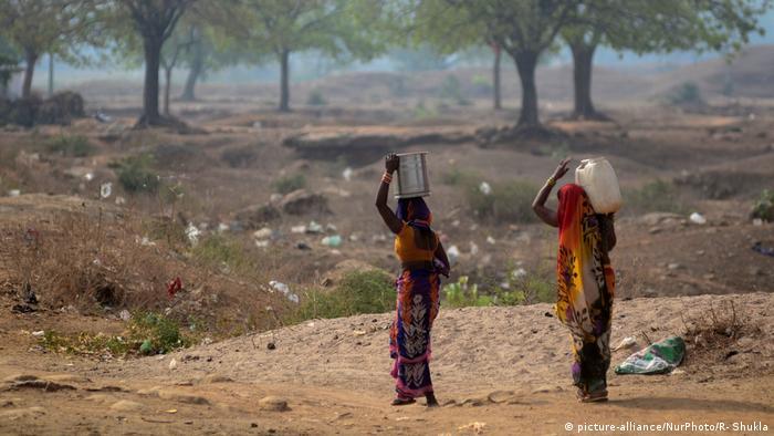 Zwei Frauen in bunten Gewändern mit Wasserkanistern auf dem Kopf