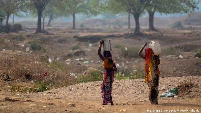 Indian local women return after carrying drinking water from a municaipal water tanker