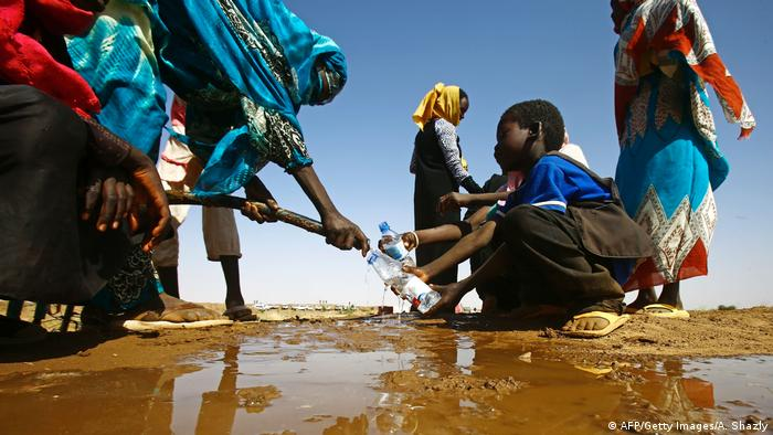 A Sudanese woman fills water bottles held by a young boy about 60 kilometres north of El-Fasher, the capital of the North Darfur state