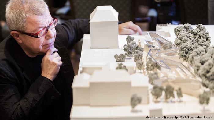 Der US-Stararchitekt Daniel Libeskind sitzt andächtig vor dem Model seines Amsterdamer Momorials.