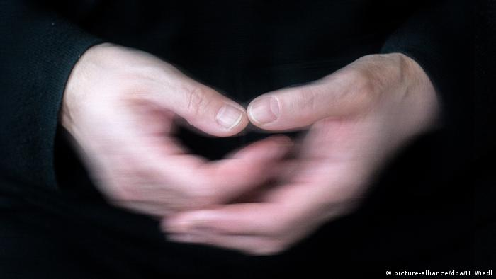 A person holding their shaky hands together