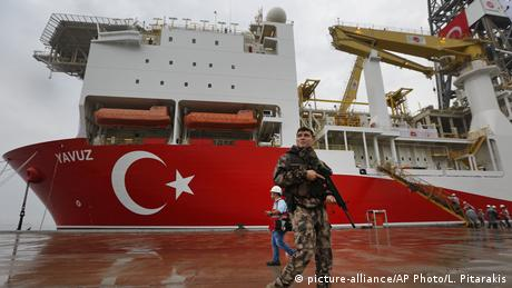 A solider with a weapon stands before a Turkish oil ship (picture-alliance/AP Photo/L. Pitarakis)