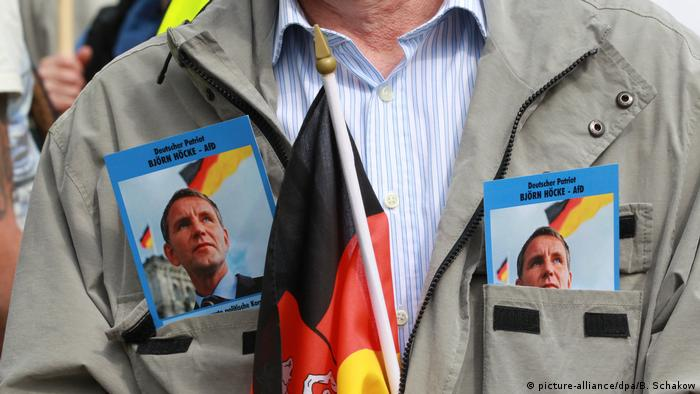 A man carries flyers showing the face of AfD state leader Björn Höcke