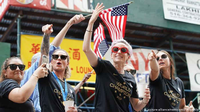 US women's soccer team players gesture while parading down New York's financial district