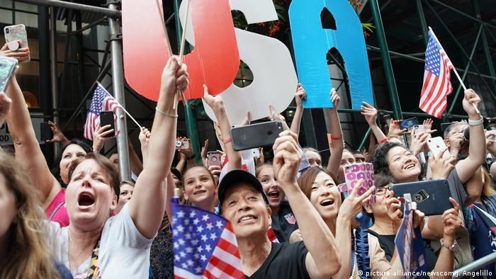 Supporters wave US flags and hold letters that spell out U-S-A