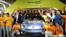 Employees pose for a picture next to a Volkswagen Beetle car during a ceremony marking the end of production of VW Beetle cars, at company's assembly plant in Puebla, Mexico, July 10, 2019. REUTERS/Imelda Medina
