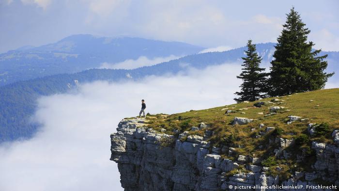 Wanderer steht an Steilwand, Creux du Van, Jura, Schweiz (picture-alliance/blickwinkel/P. Frischknecht)