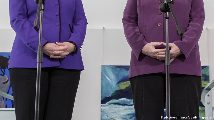 Angela Merkel, Hillary Clinton (onyl black trousers,their coats and folded hands are visible picture-alliance/dpa/M. Kappeler)