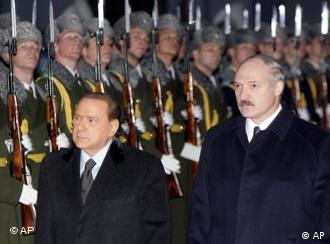 Italian Premier Silvio Berlusconi, left, and Belarusian President Alexander Lukashenko seen shortly after his arrival during an official welcome ceremony in Belarusian capital Minsk, Monday, Nov. 30, 2009. Berlusconi is on a one day official visit to Belarus. (AP Photo/Sergei Grits)
