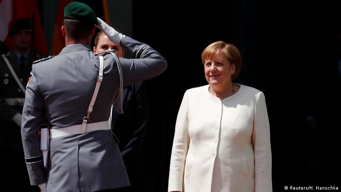 Angela Merkel stands facing a soldier who salutes her