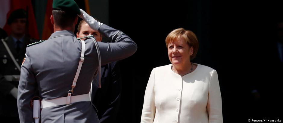 Angela Merkel stands facing a soldier who salutes her (Reuters/H. Hanschke)