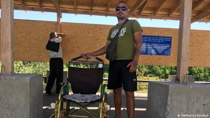 Мужчина, за деньги довозящий людей от моста к украинскому КПВВ в инвалидной коляске