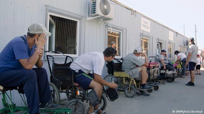 Станичные рикши за деньги подвозят людей к КПВВ на инвалидных колясках