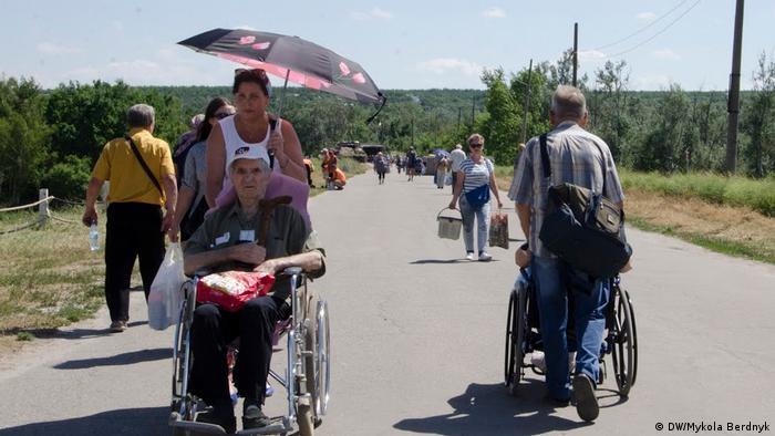 Пожилые люди и инвалиды пересекают КПВВ Станция Луганская