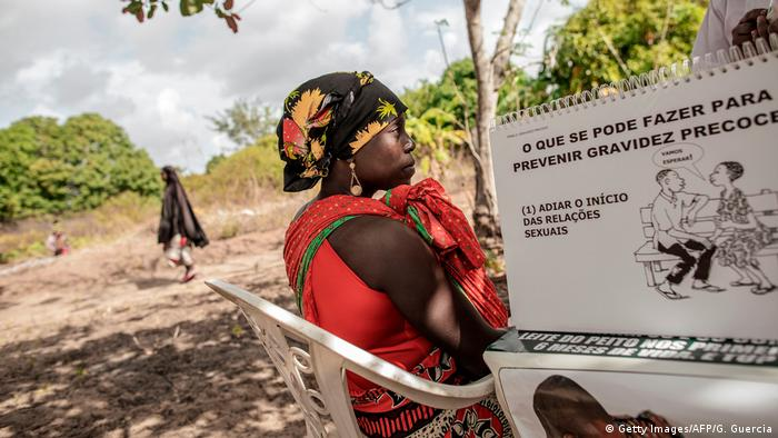 A woman carrying a child looks at a UN awareness campaign in Nampula Province, Mozambique (Archive)