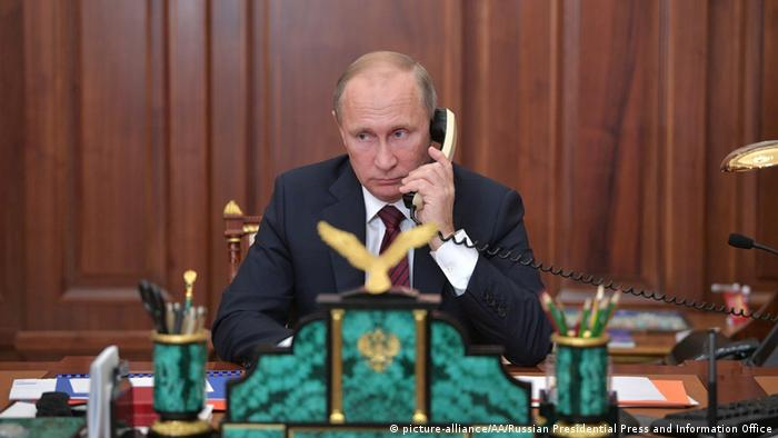 Vladimir Putin speaking on the phone in his office