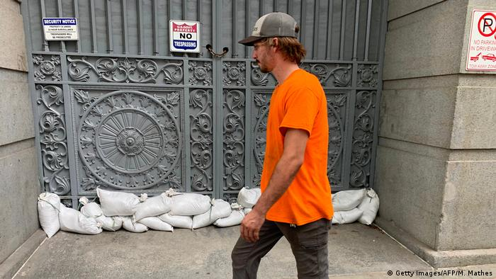 Man walking past sand bags in front of the US Customs House in New Orleans