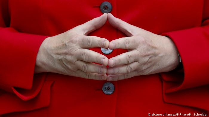 Merkel presses her hands together to make the iconic so-called Raute sign
