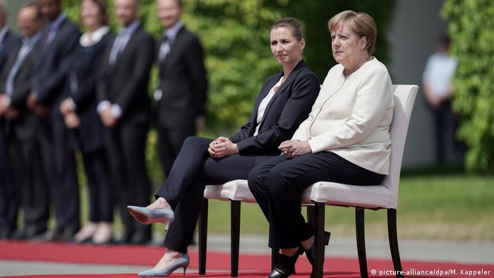Duas mulheres bem vestidas sentadas em cadeiras sobre tapetes vermelhos