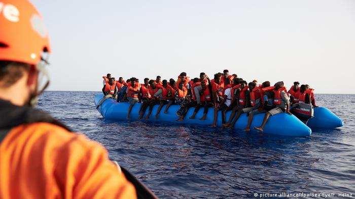 Migrants on an inflatable boat who have been rescued at sea
